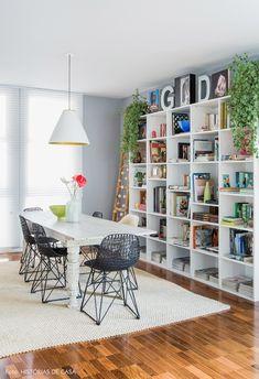 Sala de jantar tem parede cinza, estantes com livros divididos por cor e mesa de madeira rústica.