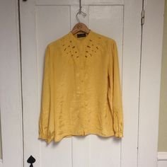 Vintage Yellow 80s Blouse Fantastic poly blend blouse with puffed sleeves and some of the most beautiful embroidery and cutouts around the neck and the sleeves. Its slightly shiny, and the shoulder pads have been removed. It is also missing the bottom button, hence the lower price. Vintage Tops Blouses