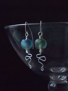 Okavango earrings by HandmadeEarringsUk on Etsy. The frosted glass beads, which were handmade in Africa from recycled bottle glass, have a wonderful 'underwater' look to them. The beads have been wrapped with aluminium wire and the tail end has been shaped to represent the sparkling Okavango River as it meanders across the Okavango Delta in Botswana, Africa.
