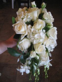 Bridal bouquet with orchids, freesia, hydrangea, and white roses.
