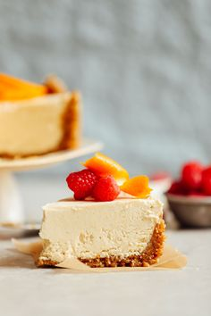Close up shot of a slice of Coconut Yogurt Cheesecake topped with raspberries and orange slices