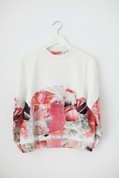 An oversized, long-sleeved cotton sweatshirt with cuffs and printed with a pink parrots pattern.