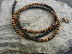 Theres a wonderful earthy, tribal look to this handmade mens necklace. Created with high quality tiger eye, black lava, brass Kenyan heishi spacers and brass drum beads, along with a touch of red jasper, and matte black onyx.  All beads are 4mm for a supple, sleek minimalist feel.  This necklace is listed as mens but also looks great on women... Comes with a brass lobster clasp. Thanks so much!! To see more go to: BraidedSouls.etsy.com \o/