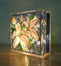 If you love flowers this one is for you! A brilliant stained glass light to enjoy in two different patterns. Lilies and roses, done on both sides of a glass block in shades of blues, very pale yellow, iridescent white, and a variety of greens. Photos were taken in with no sun, and