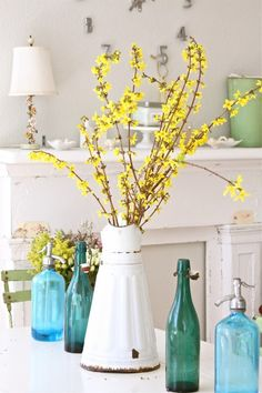 Forsythia branches placed in a worn white pitcher, among brilliant glass bottles, creates a lovely spring table.