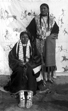 """Portrait of She Came Spotted and an unidentified Native American Sioux woman, posed outside on a fur skin rug in front of a painted backdrop of a Lakota style Indian war record, Pine Ridge Agency, South Dakota. Photo: ca. 1890. - One problem with this photograph is we're not told which one of the women is """"She Came Spotted"""", at a guess I'll go for the lady seated. At least that's a 50% chance of being right! Love the painted backdrop. Wonderful."""