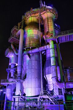 purple lighted pipes and tubes of abandoned industrial site at night