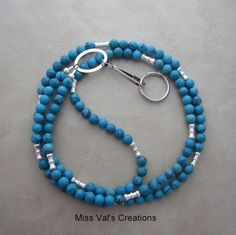Turquoise and silver lanyard for an ID badge, keys, transportation pass and more.