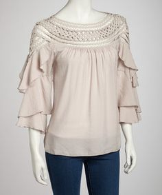 Transform an outfit into a style sensation with this lovely tunic. Dramatic ruffled sleeves are paired with a crocheted neckline, creating a look that's fashionably feminine.