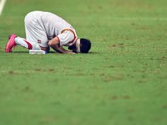 Syria's Omar Kharbin touches the ground after the final whistle against Singapore during their 2018 FIFA Group E World Cup qualifier soccer match in Singapore. Syria beat Singapore 2-1.  Roslan Rahman, AFP/Getty Images