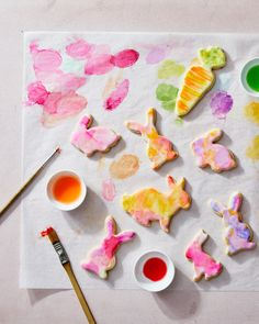 "Watercolor Easter Bunny Cookies | Martha Stewart - Sugar-cookie ""rabbits"" and ""carrots"" are frosted with royal icing and painted with a bright mixture of luster dust and water for these festive treats. Hand the kids a paintbrush and let them help decorate—it's the ultimate Easter activity! #watercolordessert #eastercookie #easterdessert"