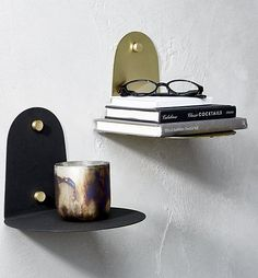 Compact disc. Matte black sconce-like shelf is as much function as it is fashion, with gold screws that give glam contrast. Hang by the bed for a space-saving charge station or in the entry to catch keys. Our favorite? Cluster on a wall with a few of your objets d'art.