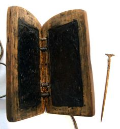 This is a reconstruction of an unknown wood framed waxed diptych and bronze stylus with four holes in each tablet bound together with a leather strap. Waxed writing tablets have been in use at least since the Greeks ca. 600 BCE in many materials as inexpensive, portable, and reusable writing surfaces.