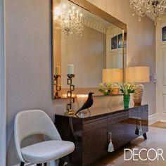 Definindo o hall, o buffet em madeira escura combina perfeitamente com o amplo espelho e o luxuoso lustre