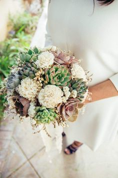 A beautiful bridal bouquet of assorted succulents, sola wood flowers, and dried blooms, wrapped in ivory satin ribbon. Shades of ivory, purple, green, and blue. The succulents can be cut from your bouquet after use and planted to enjoy for years to come! Bridesmaid Bouquet $95.00 Place orders