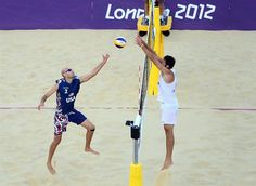 Phil Dalhausser hits the ball over the net as his opponent from Italy goes for the block during the men's beach volleyball Round of 16 at Horse Guards Parade.