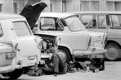 German Democratic Republic Bezirk Erfurt Erfurt - man is reparing his Trabant car on the street