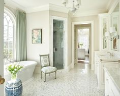 Luxurious window treatments—made from Duralee fabrics—soften the free-standing tub. Soft shades of green elevate the bathroom from a typical all-white scenario. Interior design by Lyndsy Woods. Image by Marc Mauldin. See more at www.StyleBlueprint.com.