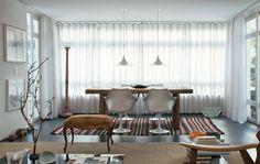 6-dicas-para-montar-sua-sala-de-jantar / Na sala de jantar, as cadeiras de braço Tulipa (Arquivovivo) e os pendentes (Reka) se contrapõem à mesa de madeira maciça (Cecilia Dale). O tapete listrado foi comprado na L'Oeil. Projeto Gustavo Calazans.