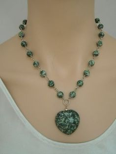 An unusual combination of contemporary design and the organic look of natural tree agate on sterling silver links. The center of the necklace is a solid heart-shaped tree agate pendant. The necklace is 17.5 inches long with an additional pendant drop of 2 inches and a sterling silver spring ring clasp. The necklace is very fluid and drapes nicely over any neckline. Every piece purchased from Silver Serenade comes in a lovely silk pouch, perfect for storage and gift giving.