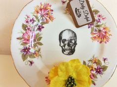 This adorable china side plate has been rescued and lovingly defaced by hand to give it a new lease of life. The pretty floral pattern has been offset by the skull detail - it is sure to be an edgy addition to any home or the perfect gift! This piece is an original vintage from the 1970s Colclough Wayside collection.  This would be perfect displayed on a shelf, mounted on a wall or used as a jewellery/trinket dish. The item measures approx 6 1/2 in width.  All items are to be kept for…