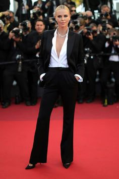 13 celebrity summer suits: Charlize Theron wears a black pants suit and low plunge white blouse