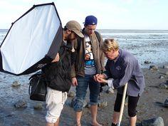 Wattführerin Anita Lohmann zeigt Fotograf Henning und seinem Assistenten, was es am Watt zu entdecken gibt (Norddeich, Niedersachsen).
