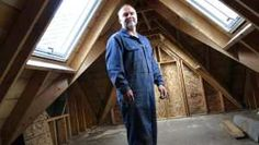 Steve Maxwell stands in the attic of a tiny home he's building. Skylights that open, a steep roof pitch and spray foam insulation make the space fully usable.