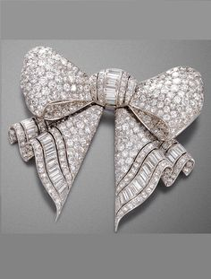AN ART DECO DIAMOND BROOCH, BY BOURDIER PARIS, CIRCA 1920. Designed as a ribbon bow, pavé set throughout with diamonds and set with a line of baquette cut diamonds to the centre knot, mounted in platinum, signed Bourdier Paris, with French assay marks. #Bourdier #ArtDeco #brooch