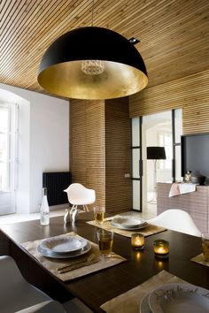 Modern kitchen with wood panels on walls and ceilign, with an oversized pendant lamp and designer chairs. Via Thedesignerpad.com