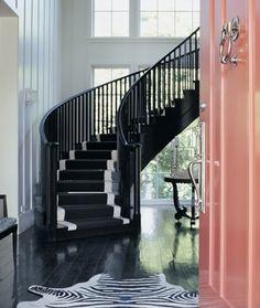 black staircase + pink front door + zebra rug in entryway amazing