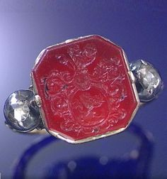 A GEORGIAN CARNELIAN INTAGLIO AND DIAMOND RING, CIRCA 1740.  Centring on an octagonal carnelian intaglio carved to depict the armorial of Lohest of Liège, set between rose-cut diamond shoulders to a scroll engraved shank carved with the profile of grotesque masks. #Georgian #antique #ring