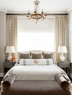 Bedroom decor ideas - dramatic window treatments as the focal point behind bed, symmetrical furniture arrangement with grey and orange colors and traditional style furnishings.