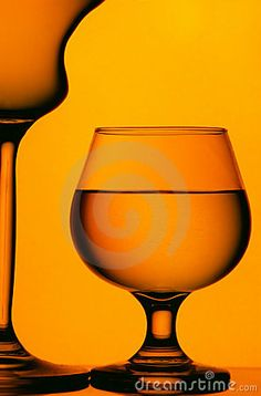 Silhouettes of wine and cognac glasses isolated on dim orange background