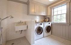 White and gray laundry room with gray cabinets accented with gray molding suspended over white front-load washer and dryer adjacent to wall with gray paneling.