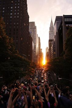 Manhattanhenge - New Yorkers gathered in the streets on Monday night 7/11/16 to watch as the sun set in alignment with the city grid, an event known as Manhattanhenge.