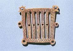 Rigid Heddle, elk horn, medieval Gotland.  I like those holes in the side. You could suspend it in a frame, maybe, or prop up a shed, or add thicker cords to the edge of the band. Just guessing.