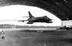 Jet flying through hanger with man on the ground