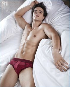 Posing in bed, Matthew Terry wears red striped LE 31 briefs.
