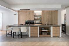 Deze strakke keuken krijgt warmte door ambachtelijk bewerkt eiken hout. Dit materiaal komt ook terug in meubels in de rest van het huis voor een mooi geheel