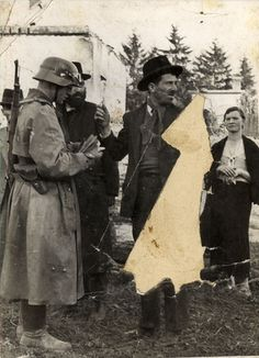 """""""A German soldier checks the identity of the Jews. The photograph was found in a dead German soldier."""""""