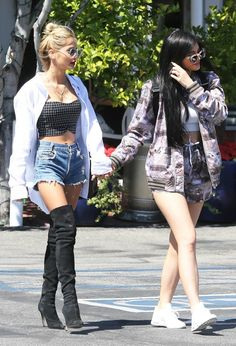 Kylie Jenner in a camo set and sneakers and Pia Mia in cut-offs and thigh-high boots.