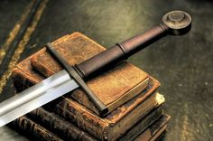 Image result for sword on a book