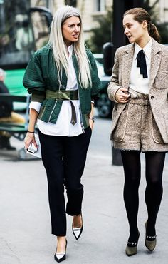 Left, a button-down shirt is worn with a belted bomber jacket, black trousers, and black and white pointed-toe heels