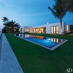 David Piscuskas of 1100 Architect and landscape architect Steven Marc Dauber collaborated with Kelly Klein on the spare scheme of her Palm Beach, Florida, home. Palm trees are placed like sculptures around the European-edge pool, which is framed by limestone coping | archdigest.com