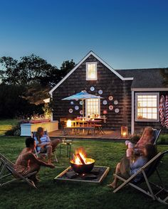 """The same wood-framing technique used to edge the garden beds was applied around the fire pit. While the sand used to level the surface absorbs charcoal and flyaway sparks, the base makes the campfire feel like a focal point. """"The fire pit is our yard's main attraction,"""" Rebecca says. """"The summer is all about unplugging for us, and it's nice to just be out there, talking and watching the fire.""""Luau lantern (on bench), oxo.com. Almidi box lantern (on deck), wrought-iron with custom paint..."""