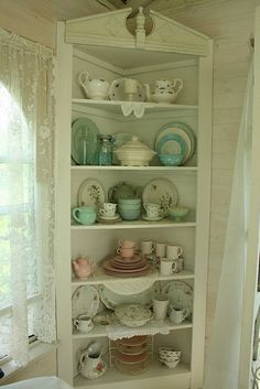 An architecturally interesting corner cabinet with a nice display of some aqua, some green, some pink, a touch of flowers here and there, but all mostly white.  Very pretty.
