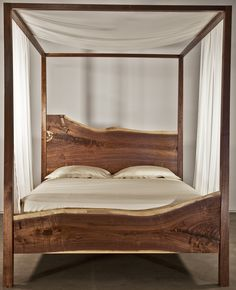 The clean, stark lines of Trace's queen black walnut canopy bed frame allows the dramatic proportion and meticulously crafted sweep of the head and foot boards to take center stage. Style and simplicity give this piece the warmth and appeal of a family heirloom. Hand rubbed oil finish with sliding dovetail construction. Purchase includes a Provenance Passport.