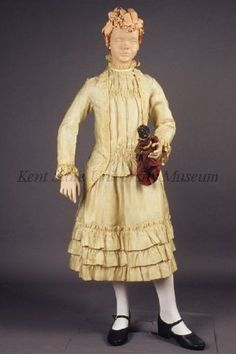 Circa 1880 fine ivory and green silk stripe gauze child's dress. Dress with 3/4 bodice, dickie with shirring at bust and hip, over bodice buttons at side and cut away to form bustle in back, fixed back with pleats, lace trim. Full skirt with 3 tiers of ruffles at hem, lace trim.