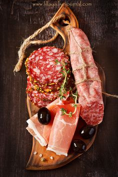Ham and salami, from top, on dark background
